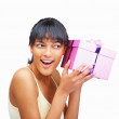 Happy young woman trying to guess what&#039;s in the gift box - Stock Photo