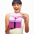 Surprised young woman peeping into her gift box - Стоковая фотография