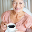 Royalty-Free Stock Photo: Closeup of a retired smiling senior woman drinking coffee
