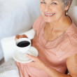 Royalty-Free Stock Photo: Senior woman drinking coffee while reading newspaper