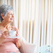 Royalty-Free Stock Photo: Senior lady with coffee cup looking to her side at copyspace