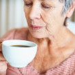 Royalty-Free Stock Photo: Senior lady blowing her hot coffee
