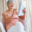 Royalty-Free Stock Photo: Happy senior woman solving a crossword puzzle in newspaper