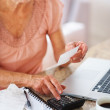 Royalty-Free Stock Photo: Retired woman budgeting her expenses using a calculator