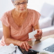 Royalty-Free Stock Photo: Senior woman calculating her financial expenses
