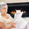 Senior woman reading a newspaper by the fireplace - Foto Stock