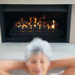 Royalty-Free Stock Photo: Retired old woman relaxing by the fireplace
