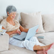 Relaxed happy elderly woman using a laptop while at home - ストック写真