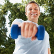 Royalty-Free Stock Photo: Smiling mature man using dumbbells outdoors