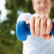 Closeup mid section of a man with a dumbbell while outdoors - Stock Photo