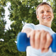 Royalty-Free Stock Photo: Happy mature man working out with a dumbbell while outdoors