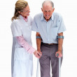 Royalty-Free Stock Photo: Nurse helping a senior man on crutches against white