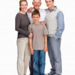 Family of four standing together against white - Stockfoto