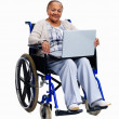 Retired old woman sitting in wheelchair with  laptop - Stock Photo