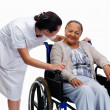 Nurse with a old woman on wheelchair looking at eachother - Stock Photo