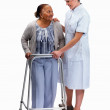 Royalty-Free Stock Photo: Nurse helping a senior woman with a walking frame