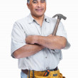 Royalty-Free Stock Photo: Mature handyman wearing a tool belt with hammer in hand