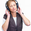 Pretty mature lady enjoying music on headphones - Stok fotoğraf