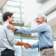 Business agreement - Senior and young executives shaking hands - Photo