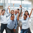 Business success - Happy multi ethnic team with hands raised - Stock Photo
