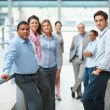 Confident business group standing in modern office environment - Stock Photo