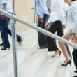 Busy business ascending on office stairs - Stock Photo