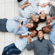 Royalty-Free Stock Photo: Business colleagues lying in circle doing various activities