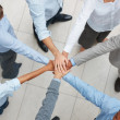 Business team with their hands together in a circle - Stock Photo