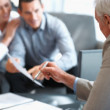 Financial planner explaining investment plans to clients - Stock Photo