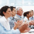 Business team applauding at conference table - Stock Photo