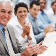 Business applauding and smiling in presentation room - Stock Photo