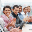 Successful business executive applauding at a conference - Stock Photo