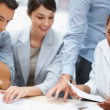 Team of a colleagues working on business plans together - Stock Photo
