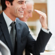 Smiling handsome business man at a board room meeting - Stock Photo