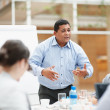 Mixed race business man speaking up at a meeting - Stock Photo