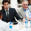 Unsatisfied business man sitting with team at the table - Stock Photo