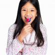 Royalty-Free Stock Photo: Cheerful little mixed race girl licking a lollipop on white