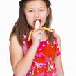 Royalty-Free Stock Photo: Portrait of a sweet young girl eating banana isolated on white