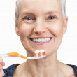 Beautiful old woman&#039;s face with a toothbrush on white - Stock Photo