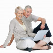 Royalty-Free Stock Photo: Studio image of casual old couple sitting with laptop on white