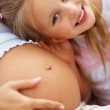 Sweet young girl listening to her mother tummy - Stock Photo