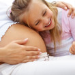 Excited young girl listening to her pregnant mother belly - Stock Photo
