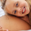 Cute young girl listening to her pregnant mother belly - Stock Photo