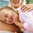 Excited cute little girl listening to her pregnant mother belly - Stock Photo