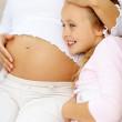 Sweet young girl with her pregnant mother - Stock Photo