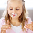 Portrait of happy cute girl with cake on her face - Stock Photo