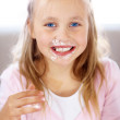 Funny little girl with cake on her face - Stock Photo
