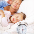 Little girl lying with parents sleeping at the back - Stock Photo