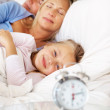Young girl smiling while her parents sleeping at back - Stock Photo