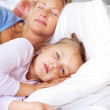 Cute little girl lying with her parents sleeping on bed - Stock Photo
